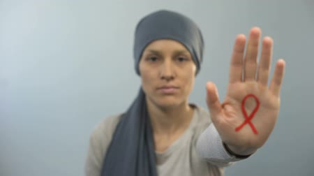 ölümcül : Red ribbon sign on womans palm showing stop gesture, AIDS awareness campaign