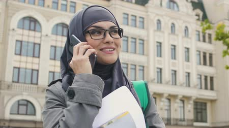 promoce : Muslim woman talking on phone, waiting near college for classes, study abroad