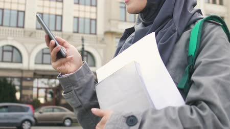 promoce : Muslim girl using phone, waiting for friends near college, education in Europe Dostupné videozáznamy