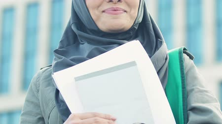 promoce : Excited Muslim woman holding tutorial books, gender equality in education