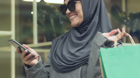 delighted : Stylish Muslim woman carrying purchases, happy shopping time, seasonal discounts