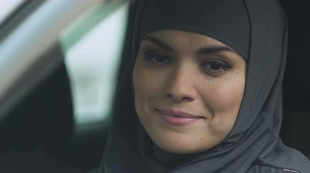 engedély : Muslim woman rolling car window down to check road, attentive driver, closeup