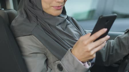 megfelel : Muslim female driver using phone while stuck in traffic jam, risk of accident Stock mozgókép