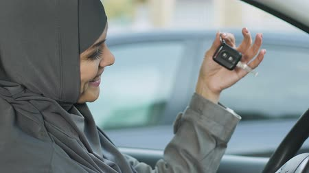 prawo jazdy : Happy Muslim woman holding keys, rights of female drivers in Islam, car purchase