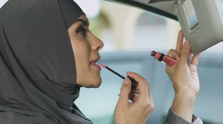 prawo jazdy : Muslim woman doing makeup in car while stuck in traffic jam, risk of accident