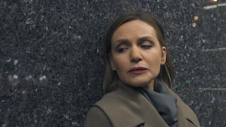 hajló : Unhappy lonely woman leaning on wall closing eyes slow motion, disappointment