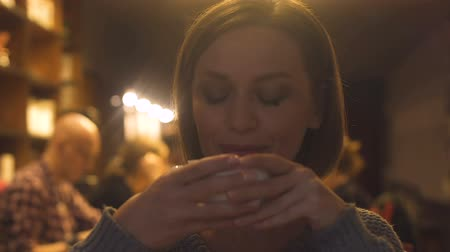 kafeterya : Happy pretty woman with cup of tea in hands enjoying taste of hot beverage, cafe Stok Video