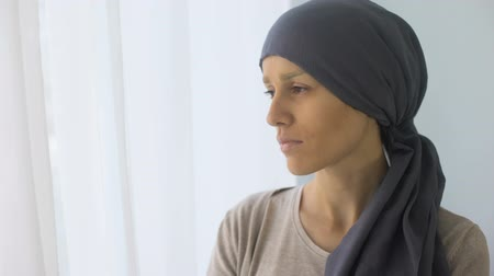 oncologia : Upset woman in headscarf looking in window, rehabilitation centre, fatal disease