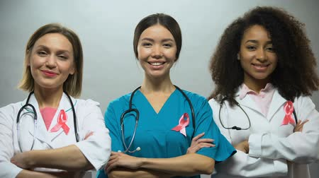 seio : Group of smiling nurses with pink ribbons, breast cancer awareness, treatment