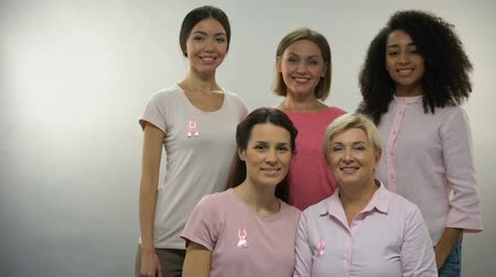 癌 : Group of women in pink shirts with breast cancer ribbons looking into camera