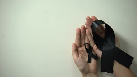 rouwen : Big and little black ribbons in hands, melanoma awareness, skin cancer treatment