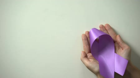 causa : Purple ribbon in lady hands, world Alzheimer disease awareness day, healthcare