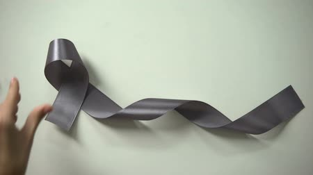 deadly : Lady putting gray ribbon on table, brain cancer awareness campaign, treatment Stock Footage