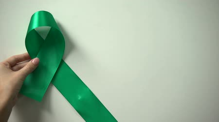 chemioterapia : Green ribbon on table, World Mental health day, awareness campaign, tolerance