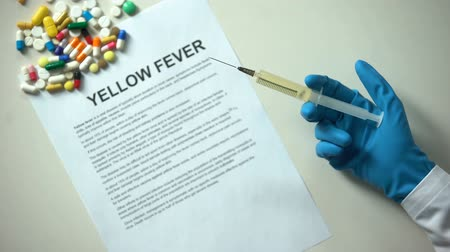 preventive : Yellow fiber word on paper, doctor hand with syringe pills and tablets on table Stock Footage