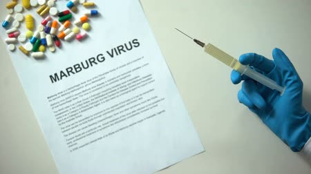 avertir : Diagnostic du virus de Marburg sur papier, main avec seringue, pilules et comprimés sur table