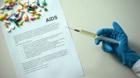 пожертвование : AIDS diagnosis written on paper, hand with syringe, pills and tablets on table Стоковые видеозаписи