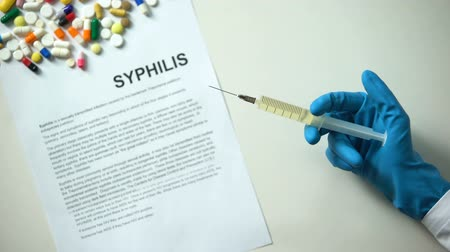 пожертвование : Syphilis diagnosis written on paper hand holding medication in syringe treatment Стоковые видеозаписи