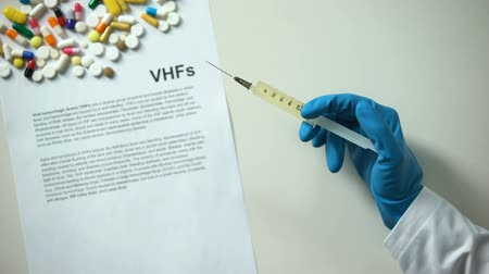 пожертвование : VHFs diagnosis written on paper, hand holding medication in syringe treatment Стоковые видеозаписи