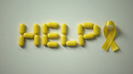 солидарность : Female placing yellow ribbon, help word made of pills on table, childhood cancer