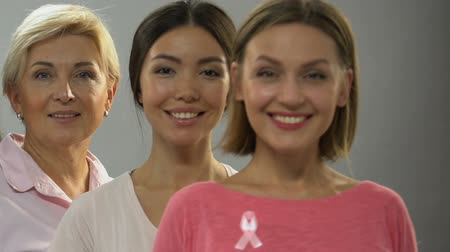 seio : Women of different age with pink ribbon smiling at camera, breast cancer control Stock Footage