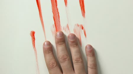 bloody hands : Bloody hand sliding down wall, victim dying, contract killing or murder closeup Stock Footage