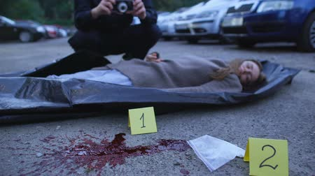 dose : Bloody female corpse and drugs lying on asphalt, police working on crime scene