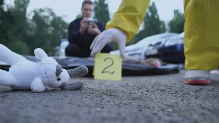 lieutenant : Forensic expert marking evidence, policeman making photo of victim, toy on road