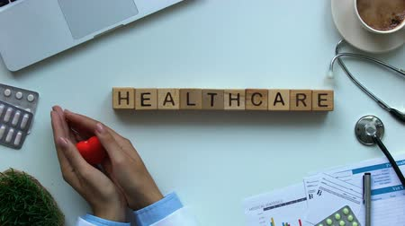 karetka : Healthcare on wooden cubes, cardiologist hands showing toy heart, diagnostics Wideo