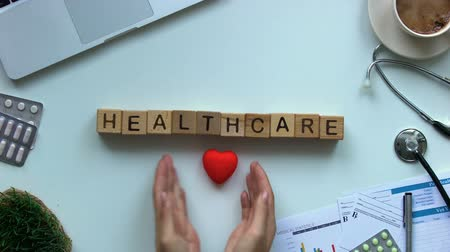 karetka : Healthcare word on cubes, doctors hands putting toy heart on table, cardiology