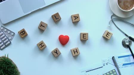 karetka : Be healthy phrase on wooden cubes moving around toy heart, medicine stop motion