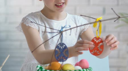 katolicizmus : Smiling girl preparing Easter decoration, hanging toy eggs on tree branches, eve