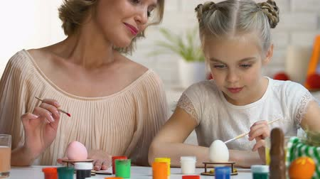 hard boiled : Mother watching daughter painting Easter egg for first time, family traditions Stock Footage