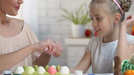 saç bantı : Daughter choosing pink egg in mothers hands, family playing in Easter games Stok Video