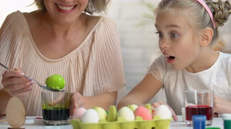 ölen : Little kid excitedly watching mom dying egg in green food coloring, Easter decor