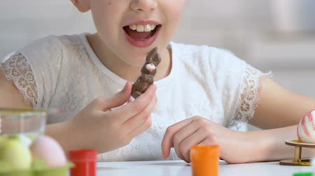 eufória : Happy little girl enjoying tasty chocolate rabbit, sweet Easter gift, childhood
