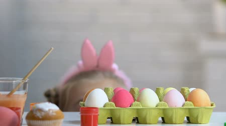 headband : Little girl appearing from under table like rabbit to enjoy brightly dyed eggs Stock Footage