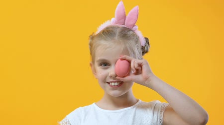 festett : Adorable child having fun holding colored egg near eye, perfect Easter mood Stock mozgókép