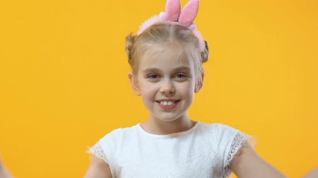ジョーク : Cute girl having fun putting colored egg to eyes on yellow background, childhood 動画素材