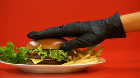 high calories : Hand in glove putting bun on hamburger, chef preparing meal, checking quality