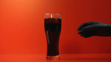 sweetened : Hand puts glass of soda, refreshing beverage rich in sugar, high calorie drink Stock Footage
