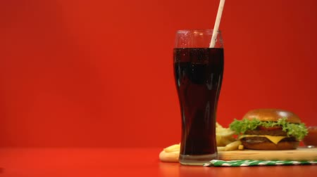 sweetened : Soft drink and hamburger, addiction to junk food, red background as warning Stock Footage
