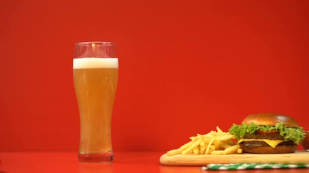 engorda : Beer foam and hamburger on red background, carbohydrates and fatty foods