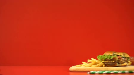 harmful habit : Male hand taking beer, hamburger and french fries disappearing, stop motion Stock Footage