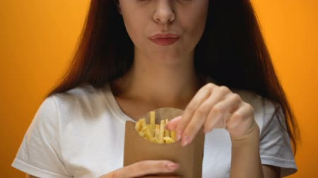 fattening : Girl eating french fries, enjoying fast food, high calorie meal, risk of obesity