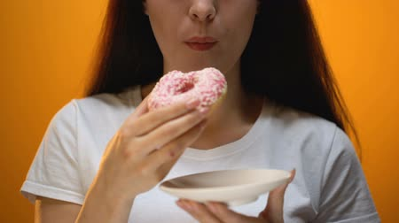sweetened : Girl eating donut, smiling to camera, addiction to sweet foods, risk of diabetes Stock Footage