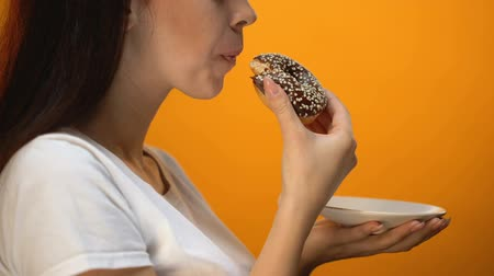 glicose : Girl biting chocolate donut, high-calorie sweet food, increased glucose diabetes