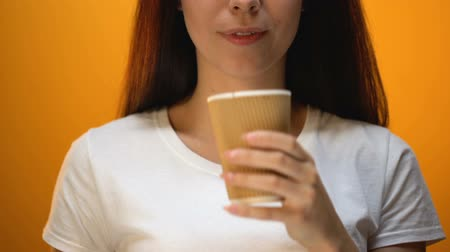 ajánlás : Girl taking off lid from plastic cup, tips to drink hot coffee properly, closeup Stock mozgókép