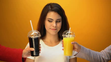 sweetened : Cheerful girl choosing soda instead of orange juice, addiction to sweet drinks