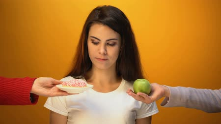 sweetened : Girl choosing apple instead of donut, natural sugar and vitamin vs confectionery